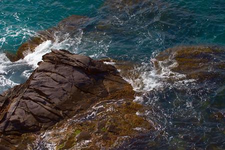 Rocks on the coast with deep blue sea on the back, horizontal image Stock Photo