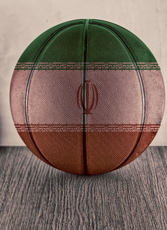 Basketball with flag of Iran, over wooden surface photo