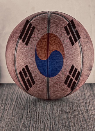 Basketball with flag of South Korea, over wooden surface photo