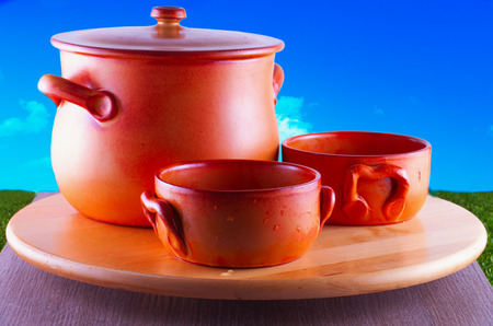 crock: Crock pots over round wooden plate, blue sky on the back Stock Photo