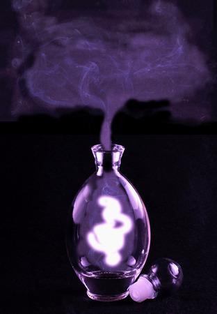 genio de la lampara: Fliud misteriosa que sale de una botella redonda, sobre el negro Foto de archivo