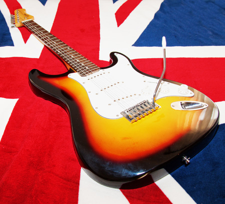 CASALE MONFERRATO, OCTOBER 5, 2014: Vision electric guitar (replica of Fender Stratocaster) over a UK flag. Fender Stratocaster is one of most famous and replied guitars in the world, and classic for British music.