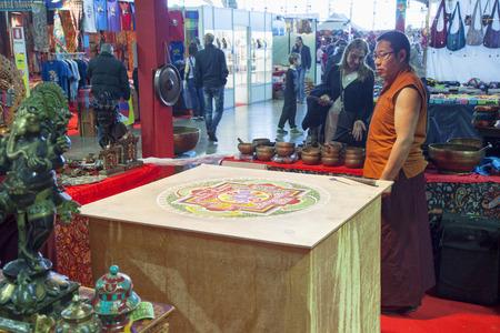 disciplines: TURIN, MARCH 27, 2015: Monk near a mandala at the Festival dellOriente, a great fair about oriental disciplines Editorial