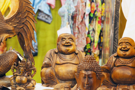 buddah: Smiling wooden buddah statue between other wooden statues horizontal image Stock Photo