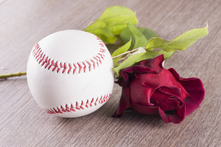 Baseball near a red rose over wooden background, horizontal image Stock Photo