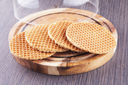Round waffel over wooden plate with bell jar horizontal image