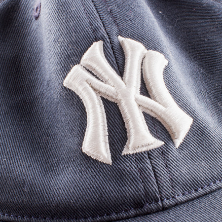 yankees: CASALE MONFERRATO, June 29, 2015: New York Yankees symbol over blue tissue. New York Yankees are the most famous american baseball franchise. Editorial