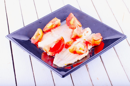 plaice: Plaice with tomatoes over black reflecting plate