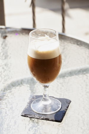 foamy: Foamy cocktail in glass over outdoor table, vertical image