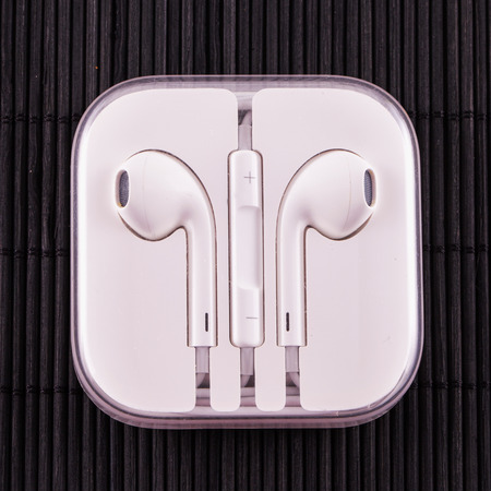 ergonomic: Ergonomic white earphones in box, over black mat background, square image Stock Photo