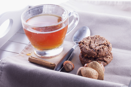 tea and biscuits: Tea, biscuits, nuts and cinnamon over tray, horizontal image