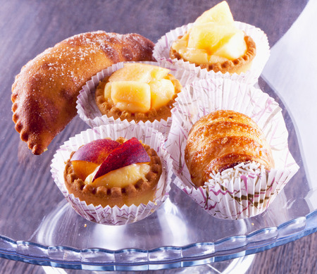 french fancy: Pastries of several kind over glass stand, horizontal image Stock Photo