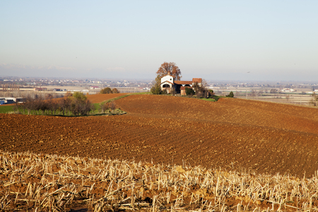 over hill: Farm over hill, in the middle of seeded fields, horizontal image