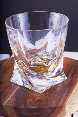 whisky glass: Whisky glass over wooden plate, vertical image