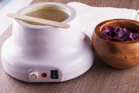Wax heater over wooden table and cup of pot pourri, horizontal image Stok Fotoğraf - 48963179