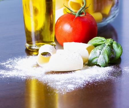 Pasta, tomato, flour, oil, basil over table, horizontal image Stock Photo