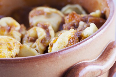 Agnolotti with sauce in clay pot in close up, horizontal image