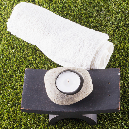square image: Candle and towel over grass, square image