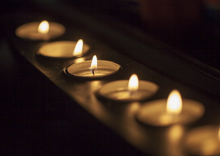 candlelight memorial: Candles in a row in a long candle holder, focus on center, in darkness, horizontal image