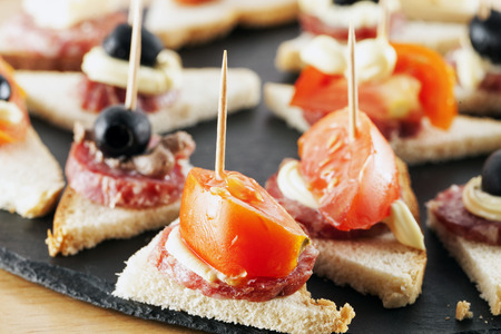 appetizers: Appetizers over black stone plate, horizontal image Stock Photo