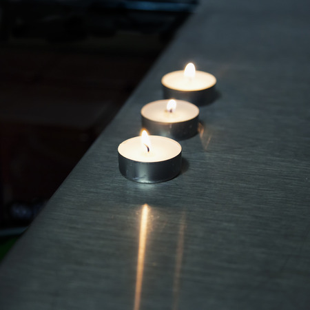 over the counter: Candles over metal bar counter, square image