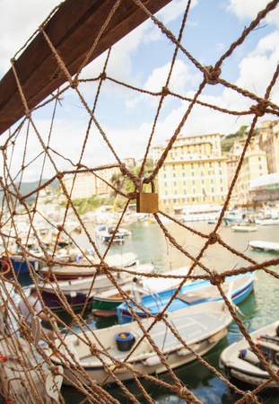 fishingnet: Fish net with boats behind, vertical image Stock Photo