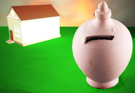 Money box with defocused house in the back, 3d rendering and photo