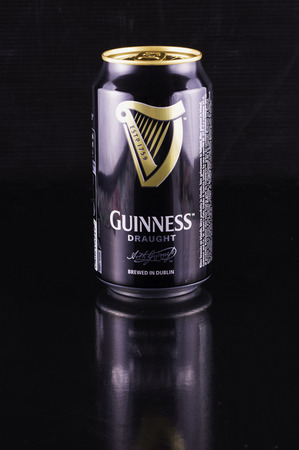 st jamess: July 6, 2016: Guinness beer can over black reflecting background. Guinness is an Irish dry stout produced by Diageo that originated in the brewery of Arthur Guinness at St. Jamess Gate, Dublin. Guinness is one of the most successful beer brands worldwide