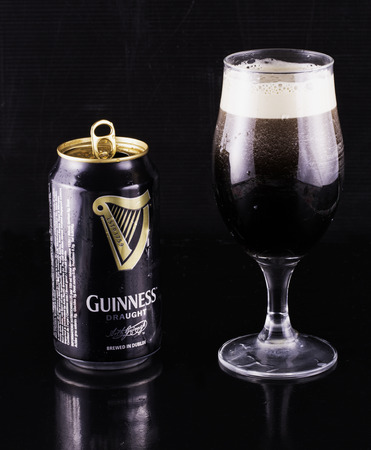 guinness beer: July 6, 2016: Guinness beer can and glass over black reflecting background. Guinness is an Irish dry stout produced by Diageo that originated in the brewery of Arthur Guinness at St. Jamess Gate, Dublin. Guinness is one of the most successful beer brands Editorial