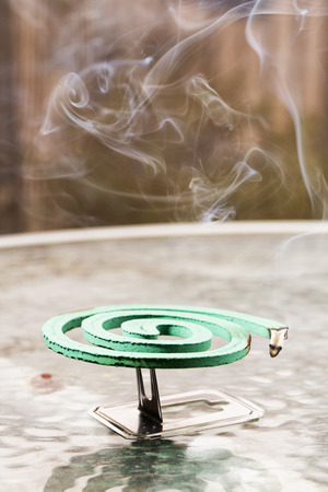 gnat: Green fumigator over glass table, vertical image