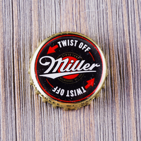 AUGUST 22, 2016: Miller beer cap over wood.Miller Brewing Company is an American beer brewing company headquartered in Milwaukee, Wisconsin