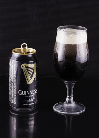 st jamess: SEPTEMBER 1, 2016: Guinness beer can and glass. Guinness is an Irish dry stout produced by Diageo that originated in the brewery of Arthur Guinness (1725–1803) at St. Jamess Gate, Dublin