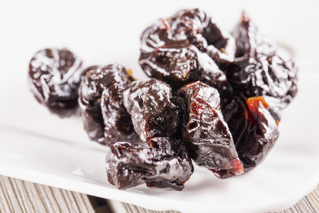 purple leaf plum: Prunes over white plate, close up, horizontal image