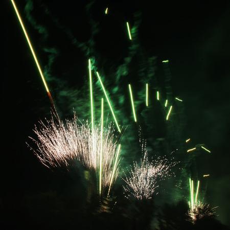 Green fireworks over black sky, square image