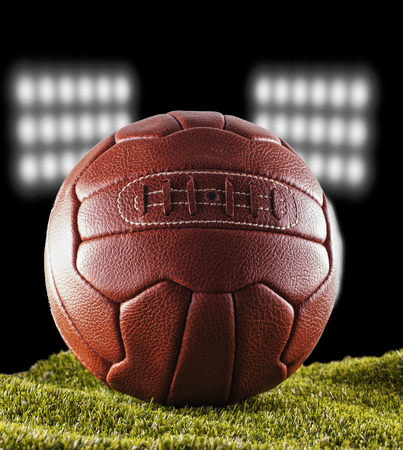 Old football over green grass with stadium lights on the back, vertical image