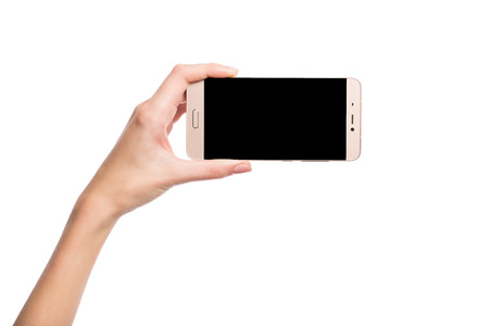 The hand holds the smartphone. Blank screen. Isolated on white.