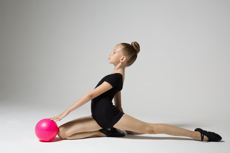 Young gymnast doing an exercise with a ball. Children's sports. Children's gymnastics. Girl