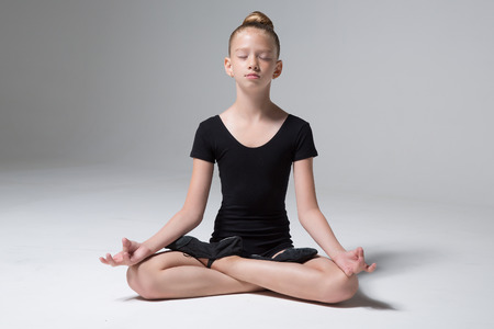 A young girl is sitting in a lotus pose. Meditation. Child. Childrens Yoga. Childrens sport. Childrens gymnastics Zdjęcie Seryjne