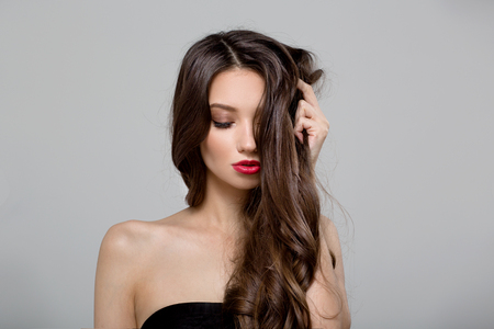 Fashion woman with curly shiny long hair. Gray background 版權商用圖片