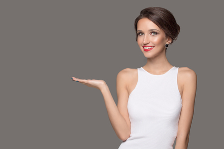 Fashion woman in white dress and beautiful smile points to a blank space. Gray background Фото со стока