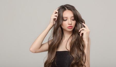 Femme de mode, confusion de cheveux. Cheveux longs ondulés et maquillage Banque d'images