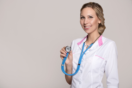 woman doctor on a gray background smiling