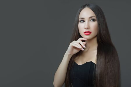 Young woman with long straight dark hair. Red lipstick perfect skin. Dark background