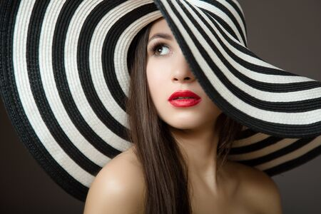 Woman in a hat and with red lips. Portrait of a young beautiful brunette. Dark background 免版税图像