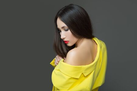 Fashion young woman in yellow clothes. Long luxurious hair and red lipstick. Dark background
