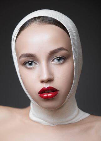Modefrauenporträt mit hellem Make-up. Lange Wimpern und rot glänzende Lippen. Gesichts-Make-up