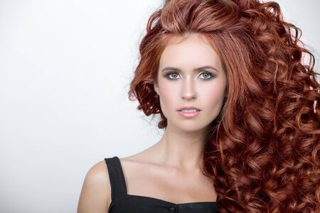 Beautiful woman with curly red thick hair. Face closeup portrait Reklamní fotografie