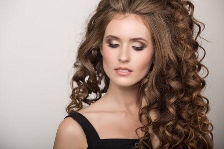 Mooie vrouw met krullend bruin dik haar. Gezicht close-up portret