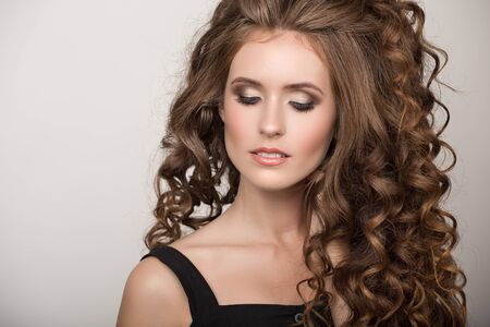 Schöne Frau mit dem lockigen braunen dicken Haar. Gesicht Nahaufnahme Porträt