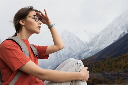 Woman traveler looks into the distance on the snowy mountains. Summer clothes and a backpack on the shoulders. Beautiful view of nature Фото со стока